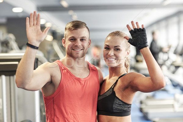 smiling man and woman waving hands in gym Stock photo © dolgachov