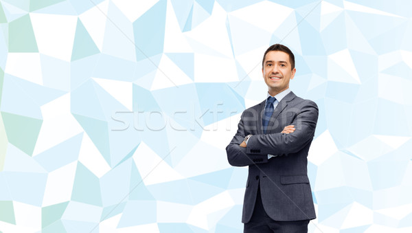 smiling businessman over blue low poly texture Stock photo © dolgachov