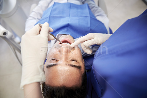 close up of dentist checking male patient teeth Stock photo © dolgachov