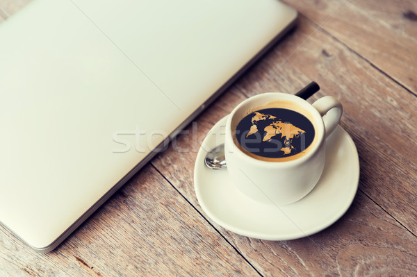 close up of laptop and coffee cup with world map Stock photo © dolgachov