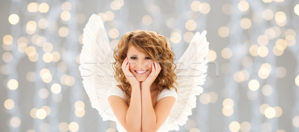 happy young woman or teen girl with angel wings Stock photo © dolgachov
