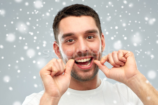 man with dental floss cleaning teeth over snow Stock photo © dolgachov