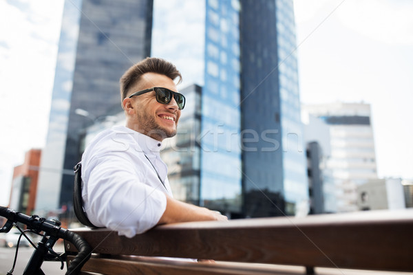 happy young man with bicycle sitting on city bench Stock photo © dolgachov