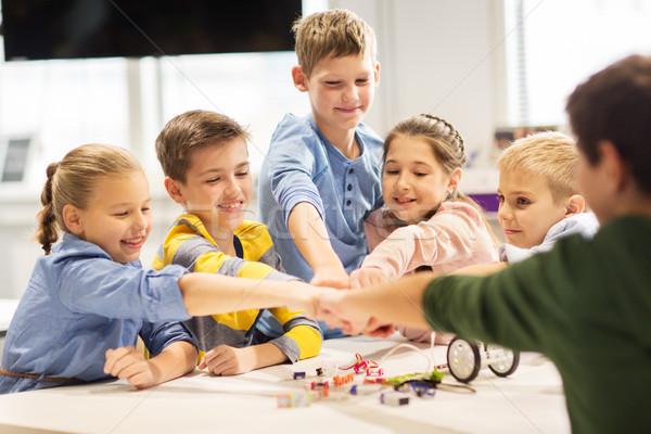 happy children making fist bump at robotics school Stock photo © dolgachov