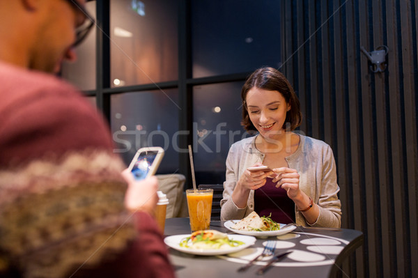 Feliz casal smartphones vegan restaurante tecnologia Foto stock © dolgachov
