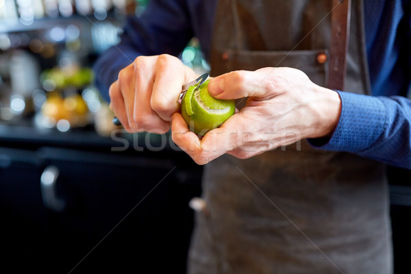 bartender removing peel from lime at bar Stock photo © dolgachov