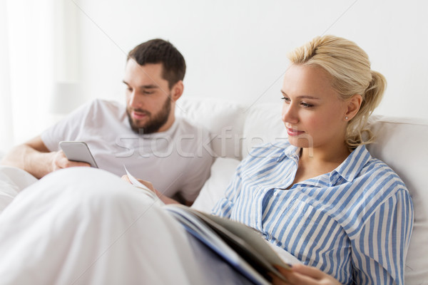 couple with book and smartphone in bed at home Stock photo © dolgachov