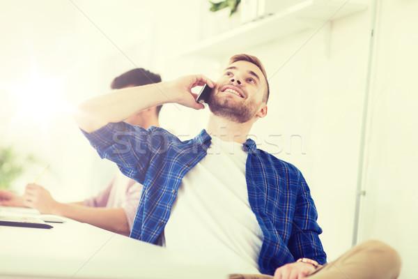 Boldog kreatív férfi hív mobiltelefon iroda Stock fotó © dolgachov