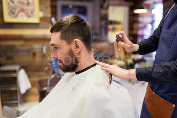 barber applying styling spray to male hair at shop Stock photo © dolgachov