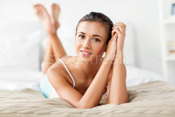 beautiful happy young woman lying on bed at home Stock photo © dolgachov