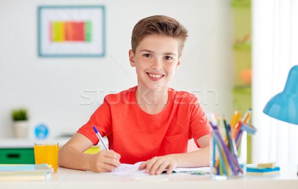 happy student boy writing to notebook at home Stock photo © dolgachov