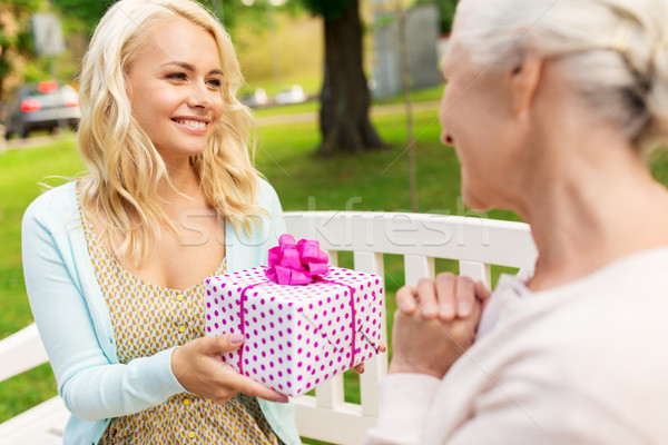 Stock photo: daughter giving present to senior mother at park