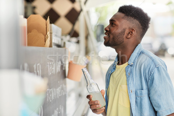 african american man with drink at food truck Stock photo © dolgachov