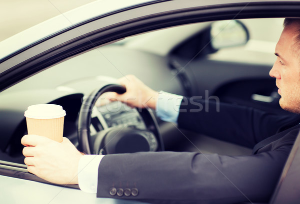 Stock photo: man drinking coffee while driving the car