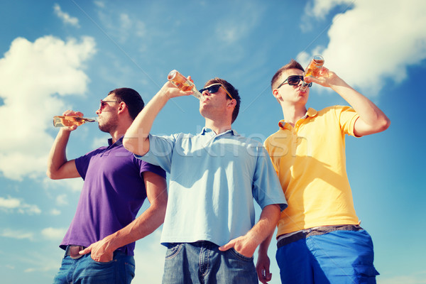 group of male friends with bottles of beer Stock photo © dolgachov