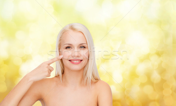 smiling young woman pointing at her cheek Stock photo © dolgachov