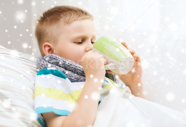 ill boy with flu in bed drinking from cup at home Stock photo © dolgachov