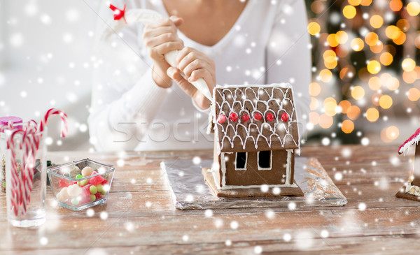 Stock photo: close up of woman making gingerbread house at home