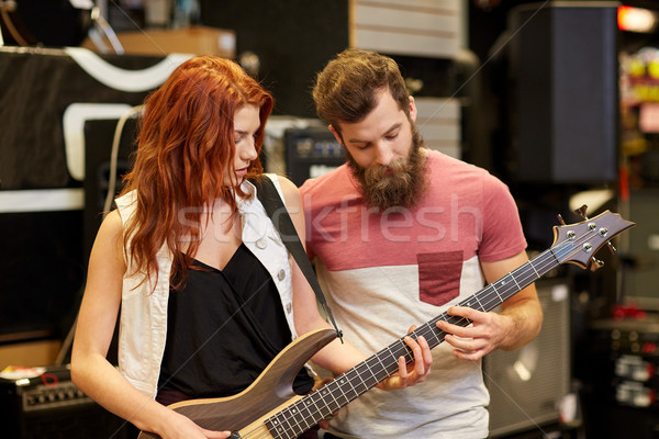 musicians playing bass guitar at music store Stock photo © dolgachov