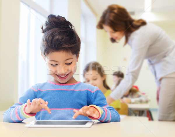 little school girl with tablet pc over classroom Stock photo © dolgachov