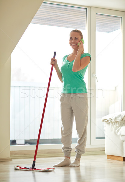 happy woman with smartphone mopping floor at home Stock photo © dolgachov
