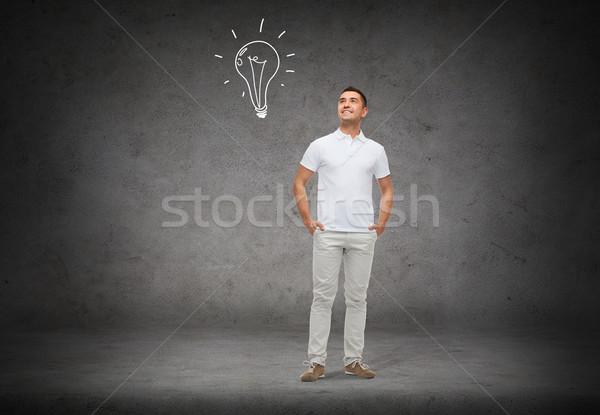 smiling man looking up to lighting bulb doodle Stock photo © dolgachov