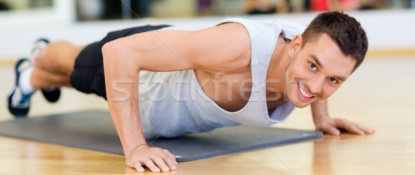 Stock photo: smiling man doing push-ups in the gym
