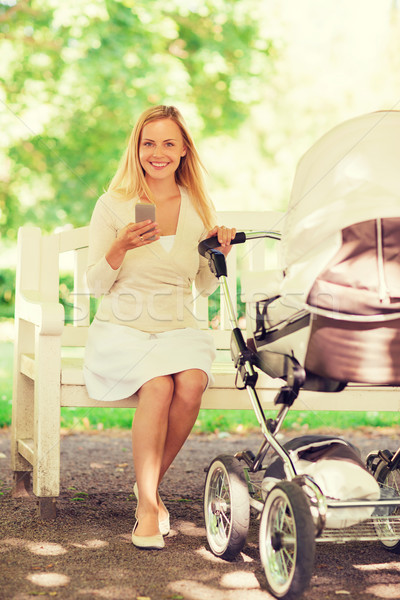 happy mother with smartphone and stroller in park Stock photo © dolgachov