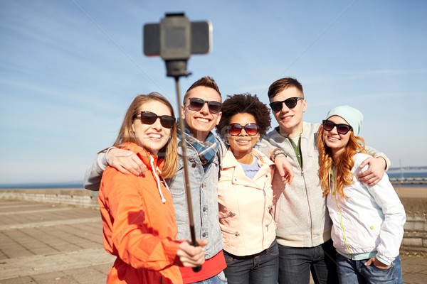 Stock photo: smiling friends taking selfie with smartphone