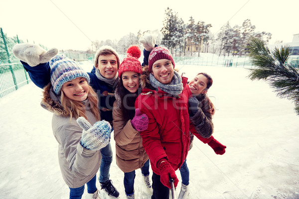 Stock photo: happy friends with smartphone on ice skating rink
