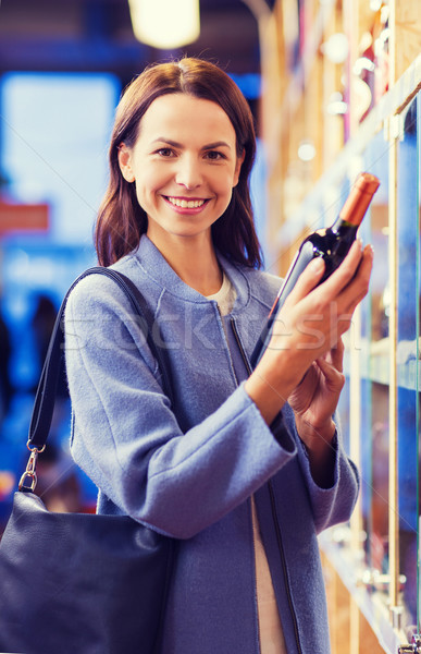 Stock photo: happy woman choosing and buying wine in market