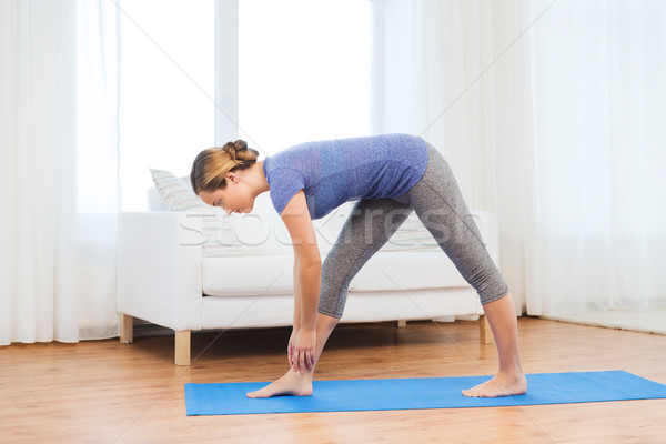 woman making yoga intense stretch pose on mat Stock photo © dolgachov