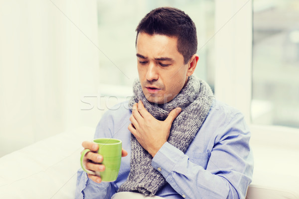 ill man with flu drinking tea and coughing at home Stock photo © dolgachov