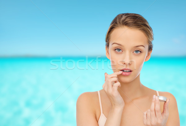 Stock photo: young woman applying lip balm to her lips