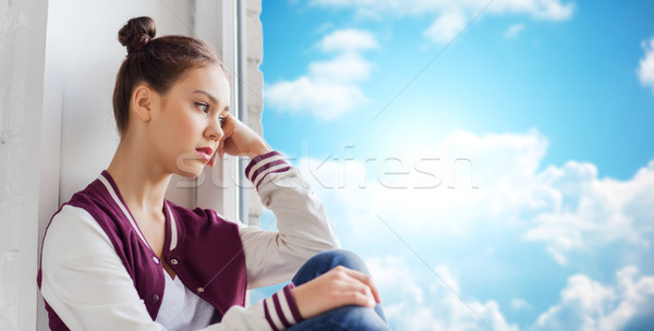 sad pretty teenage girl sitting on windowsill Stock photo © dolgachov