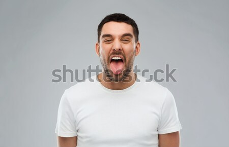 man showing his tongue over gray background Stock photo © dolgachov