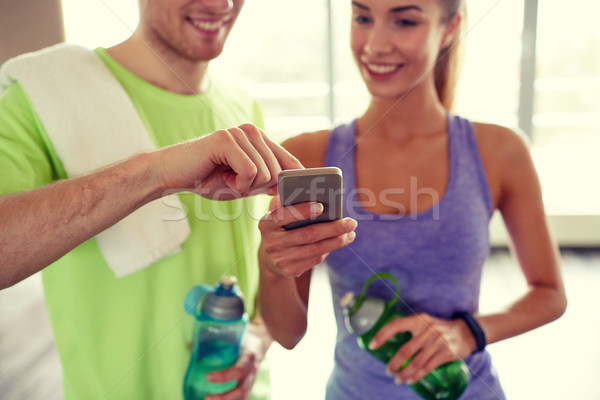 Stock photo: happy woman and trainer showing smartphone in gym