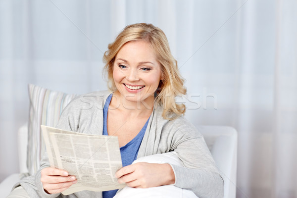 Stock photo: smiling woman reading newspaper at home