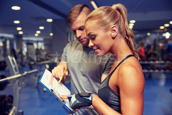 Uśmiechnięta kobieta trener schowek siłowni fitness sportu Zdjęcia stock © dolgachov