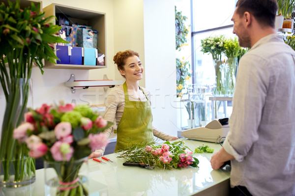 smiling florist woman and man at flower shop Stock photo © dolgachov