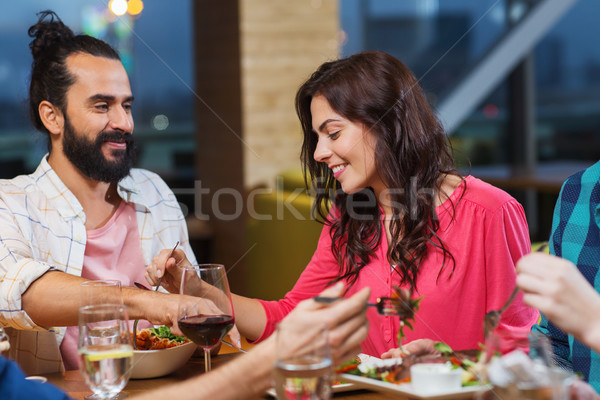 friends eating and tasting food at restaurant Stock photo © dolgachov