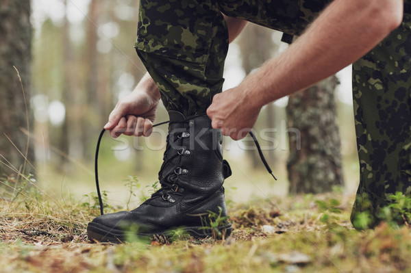 close up of soldier tying bootlaces in forest Stock photo © dolgachov