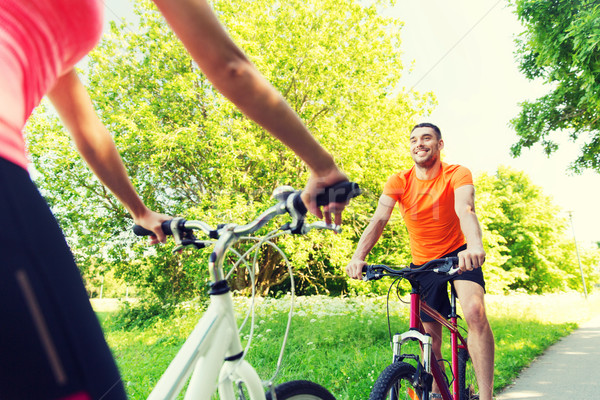 close up of happy couple riding bicycle outdoors Stock photo © dolgachov