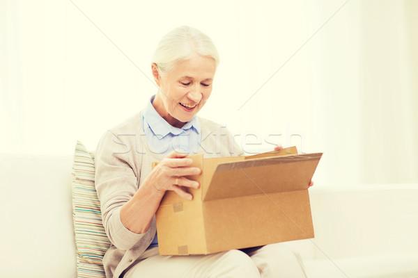 happy senior woman with parcel box at home Stock photo © dolgachov