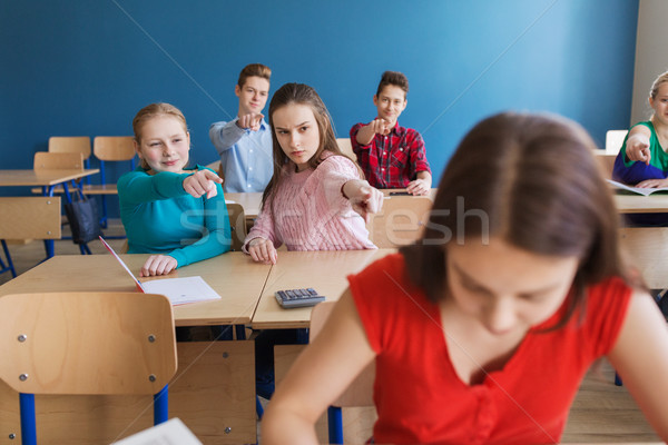 students gossiping behind classmate back at school Stock photo © dolgachov