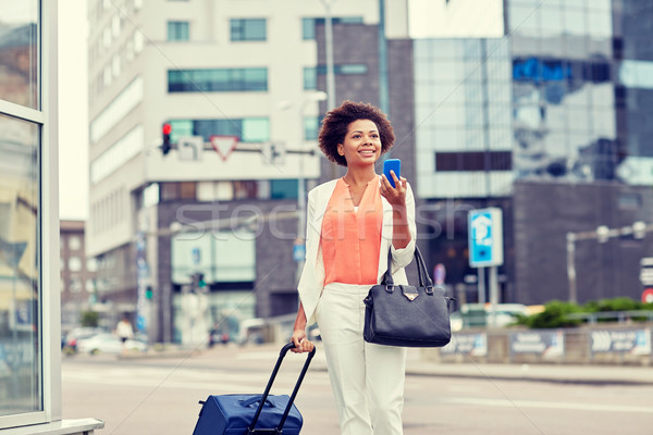 happy african woman with travel bag and smartphone Stock photo © dolgachov
