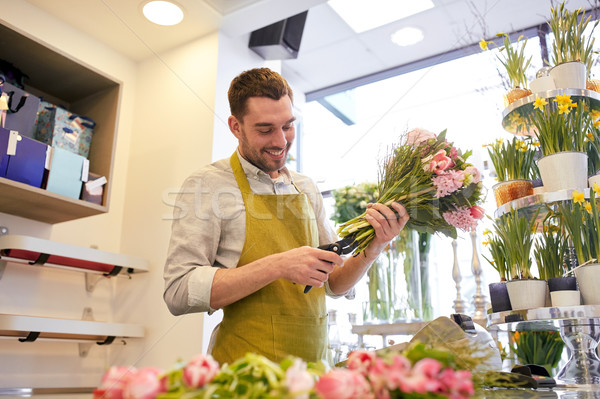 smiling florist man making bunch at flower shop Stock photo © dolgachov