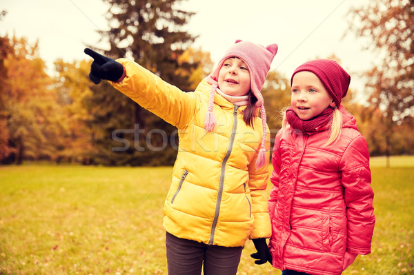 happy little girls pointing finger in autumn park Stock photo © dolgachov