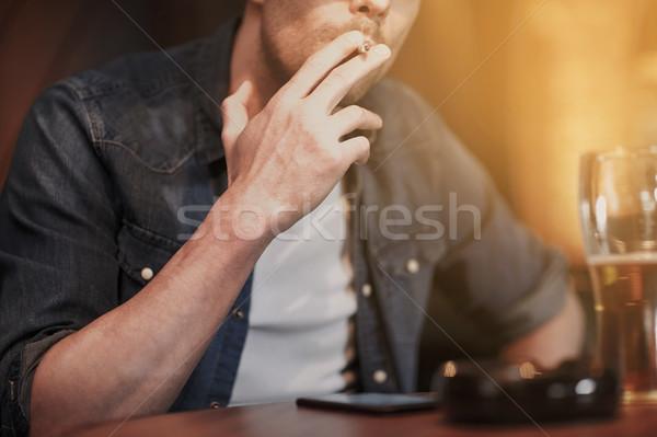 Uomo bere birra fumare sigaretta bar Foto d'archivio © dolgachov