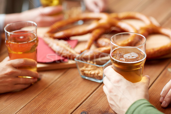 close up of men drinking beer with pretzels at pub Stock photo © dolgachov